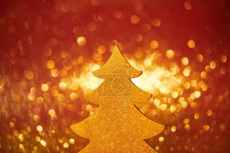 golden glittering christmas tree for decoration on red background