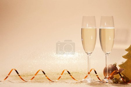 christmas toys, decorative star and two glasses of champagne with glitter on tabletop