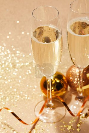 Photo for Close up of  two glasses of champagne and christmas toys with glitter on tabletop - Royalty Free Image
