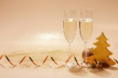 two glasses of champagne with wavy ribbon and glitter on tabletop, christmas concept