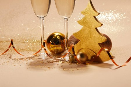 Photo for Christmas toys, golden christmas tree and two glasses of champagne with glitter on tabletop - Royalty Free Image