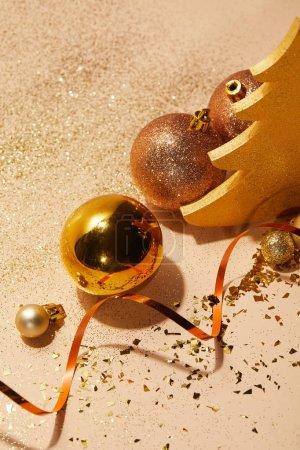 Foto de Vista de ángulo alto de bolas de Navidad, árbol de Navidad decorativo, cinta ondulada y brillo sobre mesa - Imagen libre de derechos