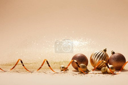 Foto de Bolas de Navidad brillante brillante y ondulada cinta en mesa color beige - Imagen libre de derechos