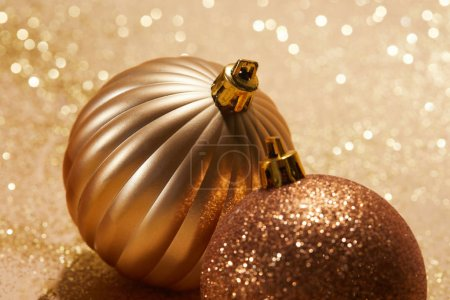 close up of shiny bright christmas balls on beige surface