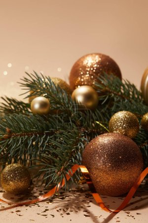 glittering christmas balls on pine branch on tabletop