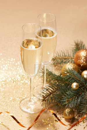 golden christmas balls, pine branch and glasses of champagne on tabletop