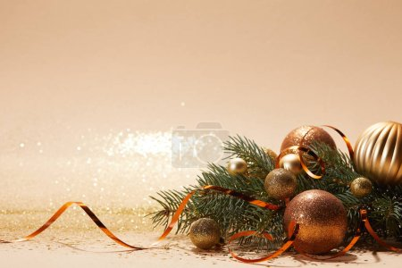 glittering christmas balls on pine branch and wavy ribbon on tabletop