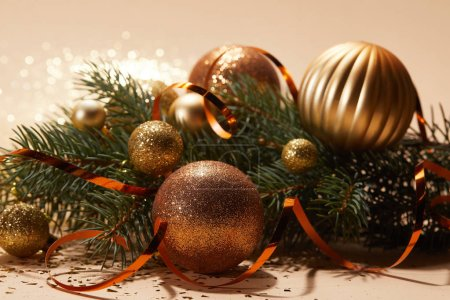 close up of glittering christmas toys on pine branch on tabletop