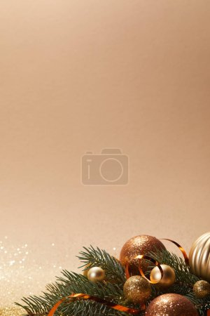glittering christmas balls on pine branch isolated on beige