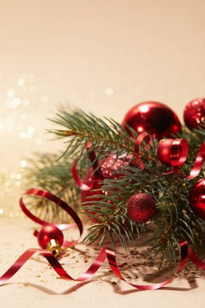 red shiny christmas balls, wavy ribbon and pine branch on glittering tabletop