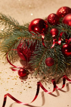 red shiny christmas toys, wavy ribbon and pine branch on glittering surface