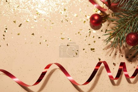 red shiny christmas balls, red wavy ribbon and pine branch on glittering surface