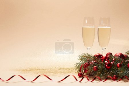 glasses of champagne, bright christmas balls and pine branch on glossing tabletop
