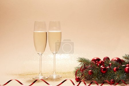 glasses of champagne, red shiny christmas balls and pine branch on tabletop with sequins
