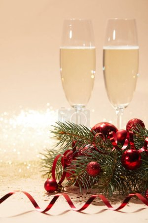 two glasses of champagne, festive christmas balls and pine branch on glittering tabletop