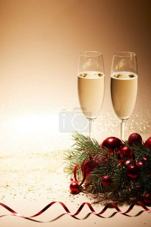 two glasses of champagne, red shiny christmas balls and pine branch on glittering tabletop