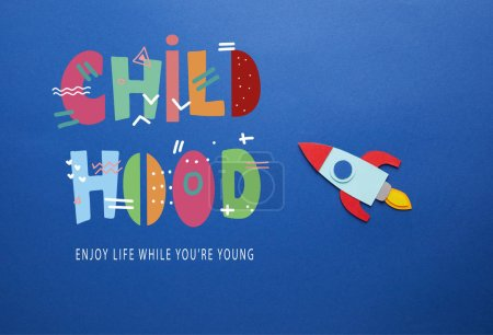 """creative rocket on blue paper background with """"childhood - enjoy life while you are young"""" lettering"""