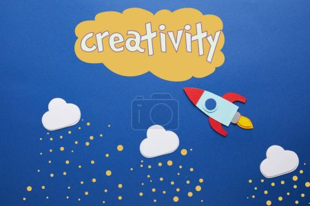 "white clouds and rocket on blue background with ""creativity"" lettering"