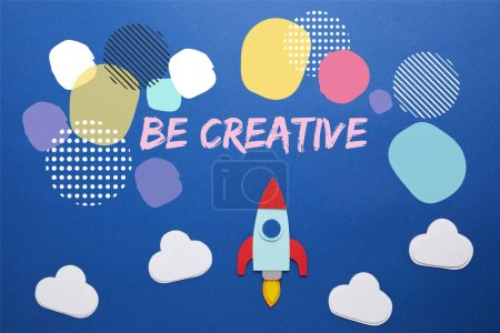 "clouds and rocket on blue paper background with ""be creative"" inspiration"