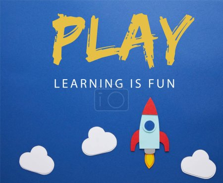 "clouds and rocket on blue paper background with ""play - lettering is fun"" lettering"
