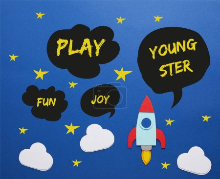 clouds and rocket on blue paper background with play, joy, fun and youngster words