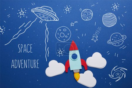 "Photo for Clouds and rocket on blue background with universe icons and ""space adventure"" inspiration - Royalty Free Image"