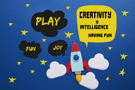 "clouds and rocket on blue background with ""creativity is intelligence, having fun"" lettering"
