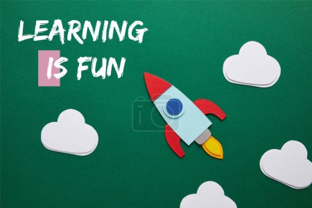 "top view of rocket and clouds on green chalkboard with ""learning is fun"" lettering"