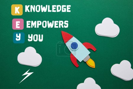 "top view of rocket and clouds on green chalkboard with ""KEY - knowledge empowers you"" inspiration"