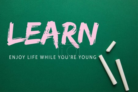 """top view of white chalks on green blackboard with """"learn - enjoy life while you are young"""" lettering"""