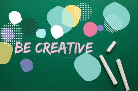 "top view of white chalks on green blackboard with ""be creative"" inspiration"