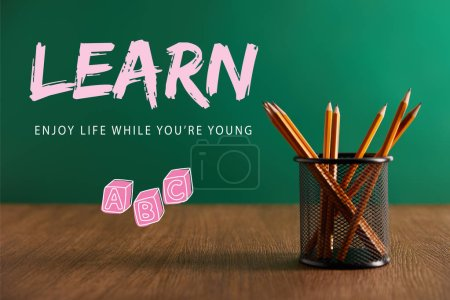"""pencils on wooden table with green chalkboard on background with """"learn - enjoy life while you are young"""" lettering"""