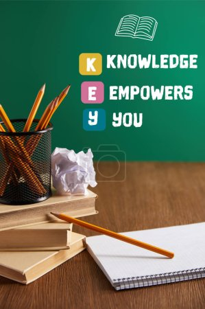 "books, copybook, crumpled paper and pencils on wooden table with ""KEY - knowledge empowers you"" inspiration"
