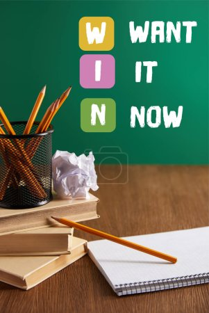 "books, copybook, crumpled paper and pencils on wooden table with ""WIN - want it now"" inspiration"
