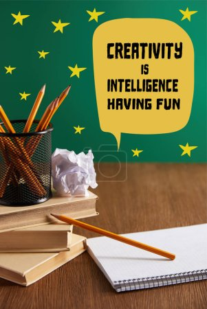 "books, copybook, crumpled paper and pencils on wooden table with ""creativity is intelligence, having fun"" lettering"