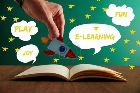 Photo pour Vue recadrée de l'enseignant tenant la fusée sur le livre ouvert avec des mots de jeu, de joie, de plaisir et d'apprentissage en ligne - image libre de droit