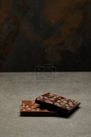 delicious chocolate bars with nuts on grey background
