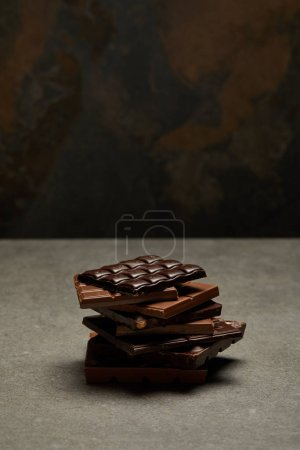 high angle view of assorted stacked chocolate pieces on grey