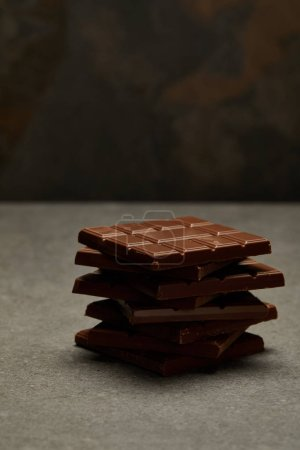 close-up view of sweet tasty stacked chocolate bars on grey background