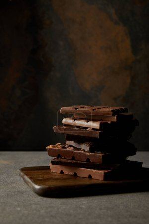 gourmet assorted chocolate pieces on wooden chopping board on grey