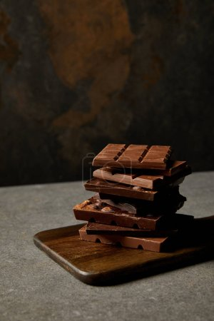 delicious assorted chocolate pieces on wooden chopping board on grey