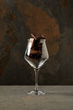 Photo for Delicious yummy chocolate pieces in glass on grey - Royalty Free Image