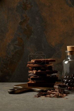 Photo for Delicious assorted chocolate pieces on chopping board and gourmet chocolate balls in glass jar - Royalty Free Image