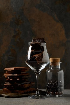 Photo for Gourmet chocolate pieces in glass and yummy chocolate balls in glass jar - Royalty Free Image