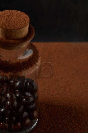 close-up view of gourmet chocolate balls in glass jar and cocoa powder