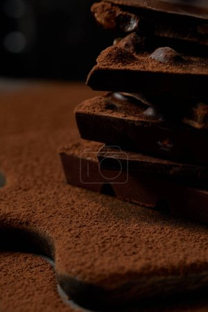 close-up view of delicious chocolate pieces with nuts and cocoa powder on chopping board