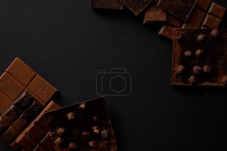 Photo for Top view of assorted delicious chocolate pieces with hazelnuts on black background - Royalty Free Image