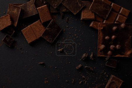 top view of assorted delicious chocolate pieces on black background