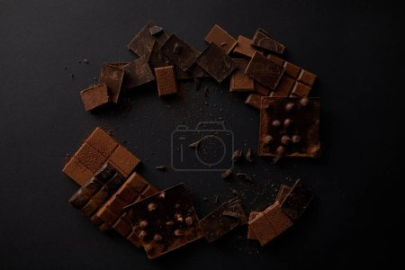 top view of assorted gourmet chocolate pieces on black background