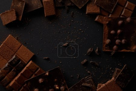 Photo for Top view of various delicious chocolate pieces on black background - Royalty Free Image